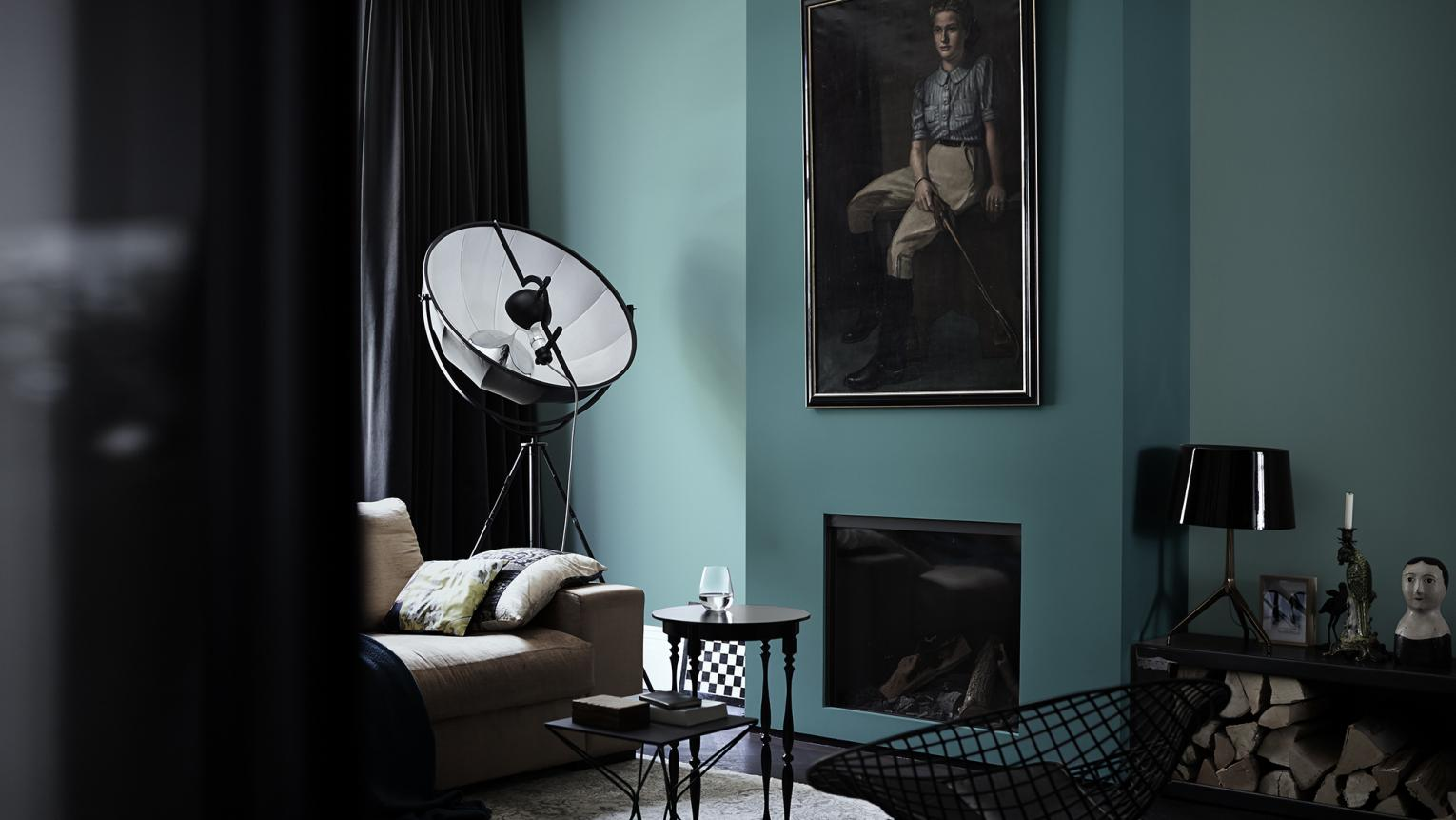 For bold living room decor ideas, contrast beautiful lagoon blue walls with furniture in black and charcoal shades.