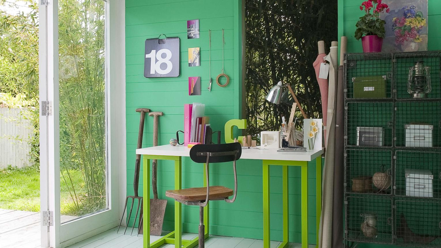 Study painted in various shades of green features a work space and a storage area.
