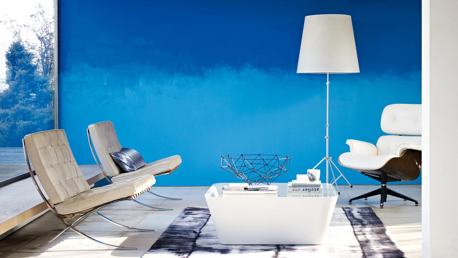 Light and dark shades of blue paint create the ombre effect on a living room wall.