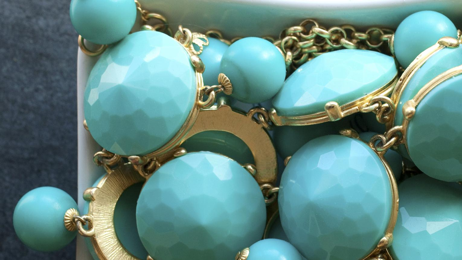 Turquoise jewels in a white porcelain dish.