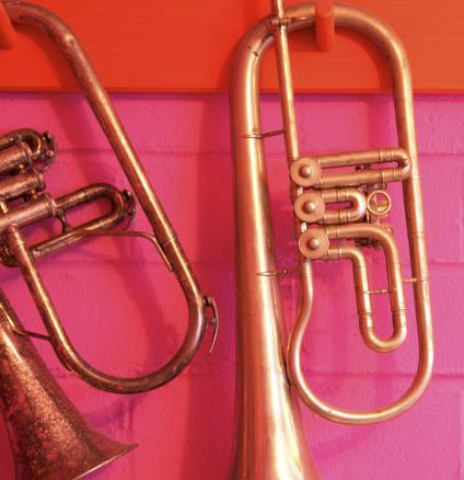 Gold trumpets against a bright pink and tangerine brick wall.