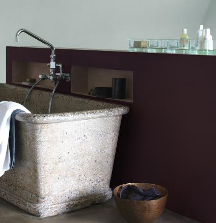 Spa style bathroom with stone bathtub and earthy colours.